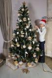 O menino no chapéu vermelho de Santa está decorando a árvore de Natal Fotos de Stock Royalty Free