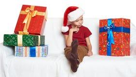 O menino no chapéu vermelho do ajudante de Santa com caixas de presente faz um desejo - conceito do feriado do Natal Fotos de Stock