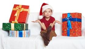 O menino no chapéu vermelho do ajudante de Santa com caixas de presente faz um desejo - conceito do feriado do Natal Foto de Stock