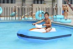 O menino no parque da água monta em uma motocicleta inflável. Fotografia de Stock