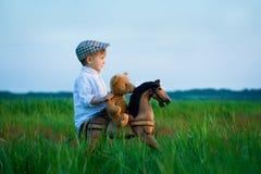 o menino no prado joga com um cavalo de balanço e um urso de peluche imagem de stock