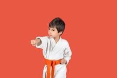 O menino no quimono branco do karaté com uma correia alaranjada Fotos de Stock