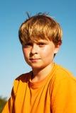 O menino no t-shirt alaranjado está olhando o auto confiável Imagem de Stock Royalty Free
