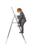 O menino no terno levanta-se no step-ladder Fotografia de Stock