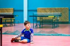 O menino no uniforme dos esportes senta-se no assoalho no gym fotos de stock