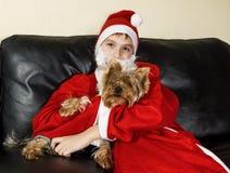 O menino no vestido Santa Claus levanta com um cão pequeno Fotografia de Stock Royalty Free
