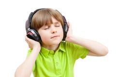 O menino nos fones de ouvido aprecia a música Fotos de Stock Royalty Free