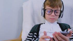 O menino nos vidros ? m?sica de escuta nos fones de ouvido no smartphone que senta-se na poltrona em casa vídeos de arquivo