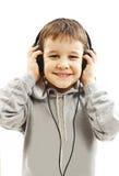 O menino novo é de sorriso e de escuta a música fotografia de stock royalty free