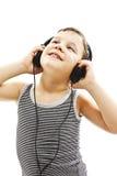 O menino novo é de sorriso e de escuta a música, olhando acima Imagens de Stock Royalty Free