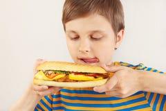 O menino novo é lambido no cheeseburger saboroso no fundo branco foto de stock royalty free