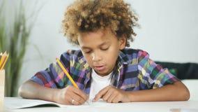 O menino novo afro-americano está sentando-se na mesa de jantar e está fazendo-se trabalhos de casa da escola video estoque