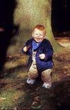 O menino novo aprecia andar na floresta fotografia de stock