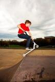 O menino novo aprecia montar um 'trotinette' Imagem de Stock Royalty Free