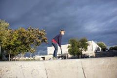 O menino novo aprecia patinar com um 'trotinette' Imagens de Stock Royalty Free