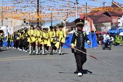 O menino novo atua enquanto o líder da faixa conduz sua equipe musical durante a exposição anual da banda filarmônica em honra do fotos de stock