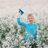 O menino novo com plano de papel e o branco colocam flores imagens de stock royalty free