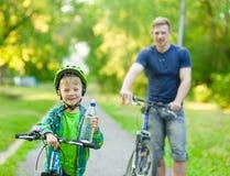 O menino novo com uma garrafa da água está aprendendo montar uma bicicleta com Imagens de Stock Royalty Free