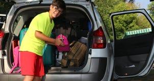 O menino novo com vidros carregou a bagagem no tronco Imagem de Stock