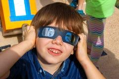 O menino novo com vidros do eclipse solar olha acima no céu como imagens de stock royalty free