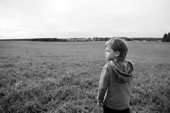 O menino novo considerável olha o campo e os sonhos fotografia de stock royalty free
