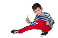 O menino novo da forma mantém seus polegares Foto de Stock