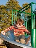 O menino novo de sorriso na camisola no campo de jogos desliza Imagens de Stock Royalty Free