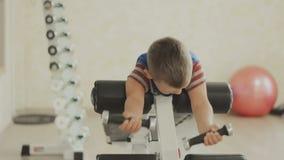 O menino novo de sorriso que faz o peso pesado exercita para o bíceps vídeos de arquivo