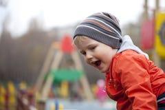 O menino novo de três anos no campo de jogos Foto de Stock