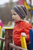 O menino novo de três anos no campo de jogos Fotografia de Stock