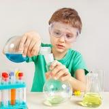 O menino novo em óculos de proteção de segurança estuda a prática química no laboratório Imagens de Stock Royalty Free