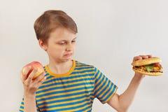 O menino novo escolhe entre o fastfood e a dieta saudável no fundo branco fotos de stock royalty free