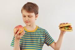 O menino novo escolhe entre o fastfood e o fruto no fundo branco imagem de stock royalty free
