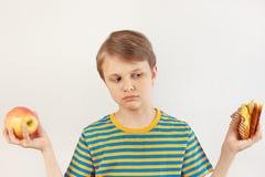 O menino novo escolhe entre o sanduíche e a dieta saudável no fundo branco imagem de stock royalty free