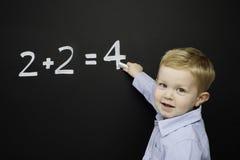 O menino novo esperto estêve a escrita em um quadro-negro Fotografia de Stock