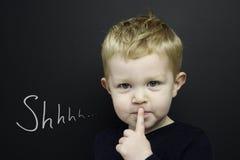 O menino novo esperto estêve o infront de um quadro-negro Imagens de Stock Royalty Free