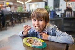 O menino novo está comendo o profiterole com gelado fotografia de stock royalty free