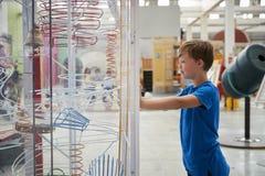 O menino novo está de vista uma exibição da ciência, vista lateral imagem de stock