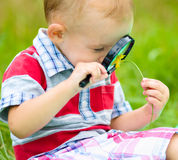 O menino novo está olhando a flor através da lente de aumento Imagens de Stock Royalty Free