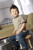 O menino novo feliz joga bandejas dos potenciômetros da cozinha das batidas como cilindros Fotos de Stock