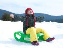O menino novo feliz tem o divertimento no vacatioin do inverno na neve fresca fotos de stock