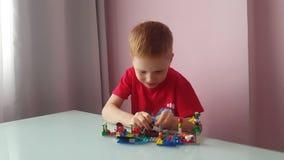 O menino novo joga o jogo do papel com construção de Kit And Talk vídeos de arquivo