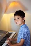 O menino novo joga um piano Imagem de Stock