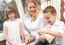 O menino novo lê a suas matriz e irmã Foto de Stock Royalty Free