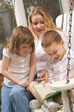 O menino novo lê a suas matriz e irmã Fotografia de Stock Royalty Free