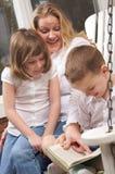 O menino novo lê a suas matriz e irmã Fotografia de Stock