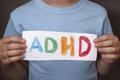 O menino novo mantém o texto de ADHD escrito na folha de papel foto de stock