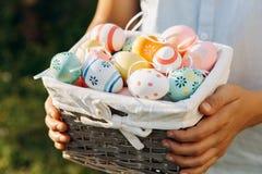O menino novo na camisa azul guarda a cesta de madeira com os ovos pintados à mão nas mãos na luz solar no jardim da mola Caça do imagem de stock
