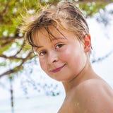 O menino novo na praia é de sorriso e de vista auto-confiante imagem de stock