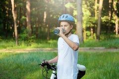 O menino novo no capacete e no ciclista branco da camisa de t bebe a água da garrafa no parque Menino bonito de sorriso na bicicl fotografia de stock royalty free
